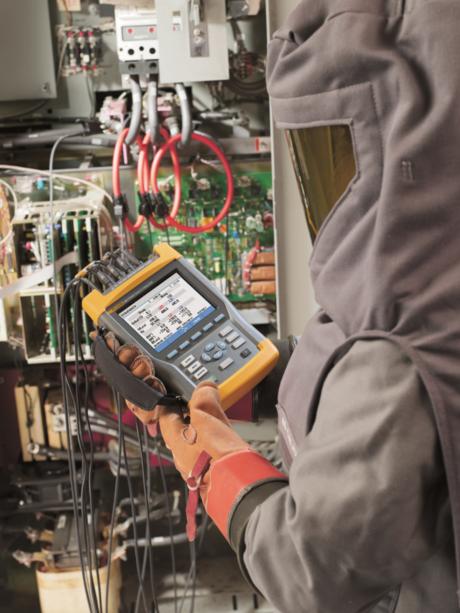 Personell bruker en Fluke 435 serie ii nettkvalitets- og energianalysator i et industrielt miljø, iført vernedrakt